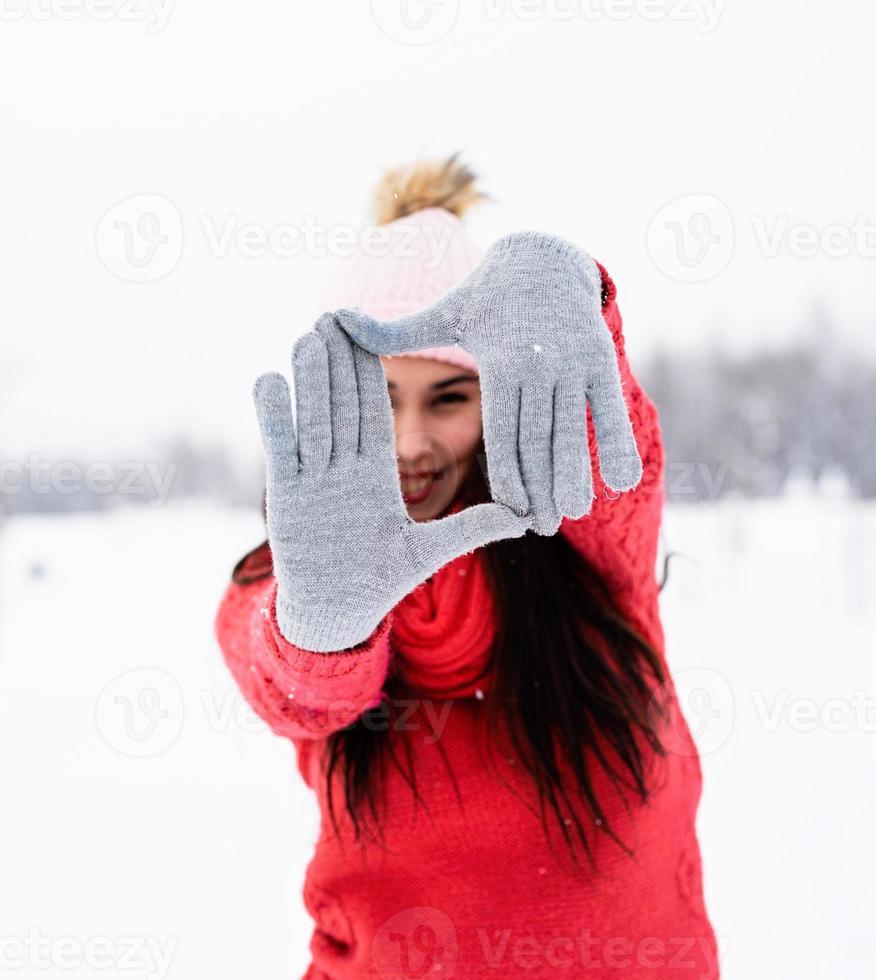 femme en pull rouge faisant signe de cadre avec ses mains photo