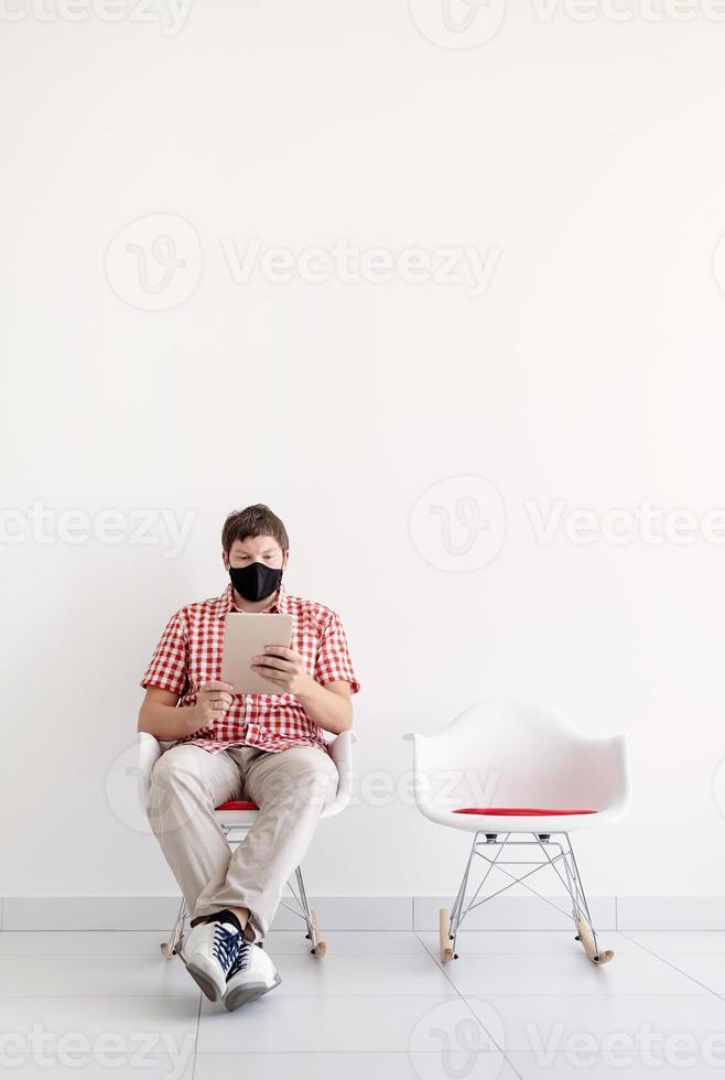 jeune homme portant un masque de protection étudiant en ligne en gardant une distance sociale photo