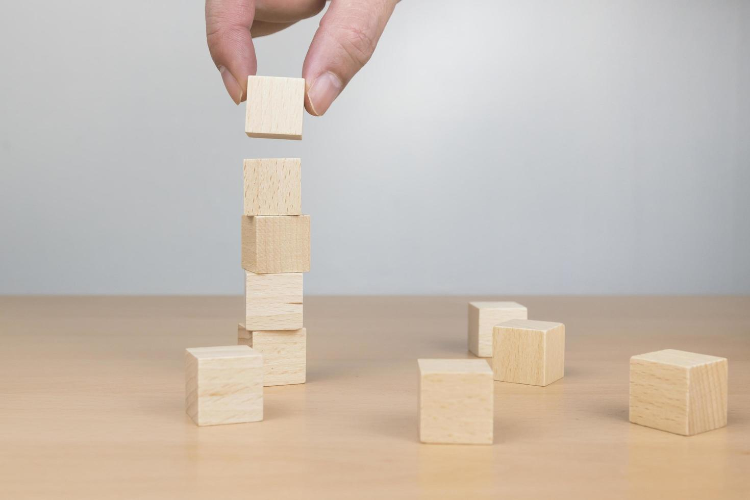 main organisant l'empilement de blocs de bois comme marche d'escalier sur une table en bois photo