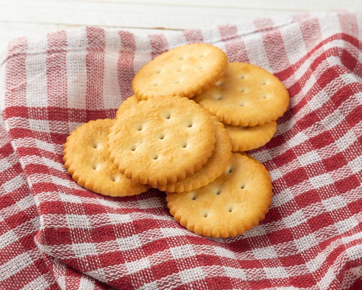 biscuits craquelins avec nappe sur fond de table en bois blanc photo