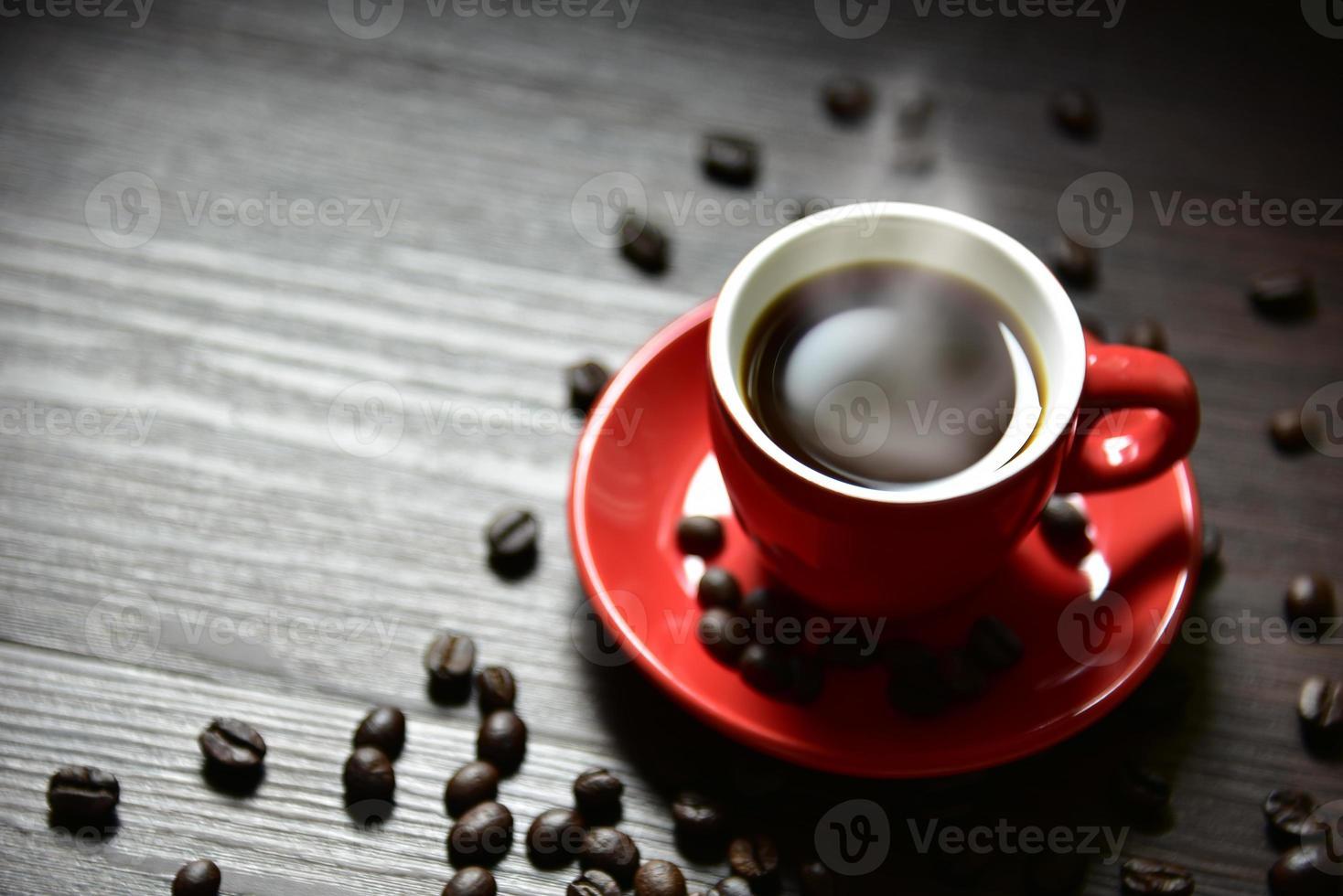 tasse de café rouge avec vapeur de flux et grain de café photo