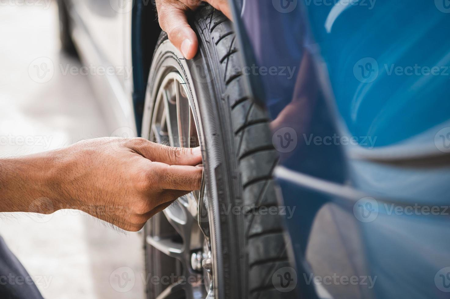 Technicien automobile masculin en gros plan enlevant le bouchon d'azote de la valve des pneus photo