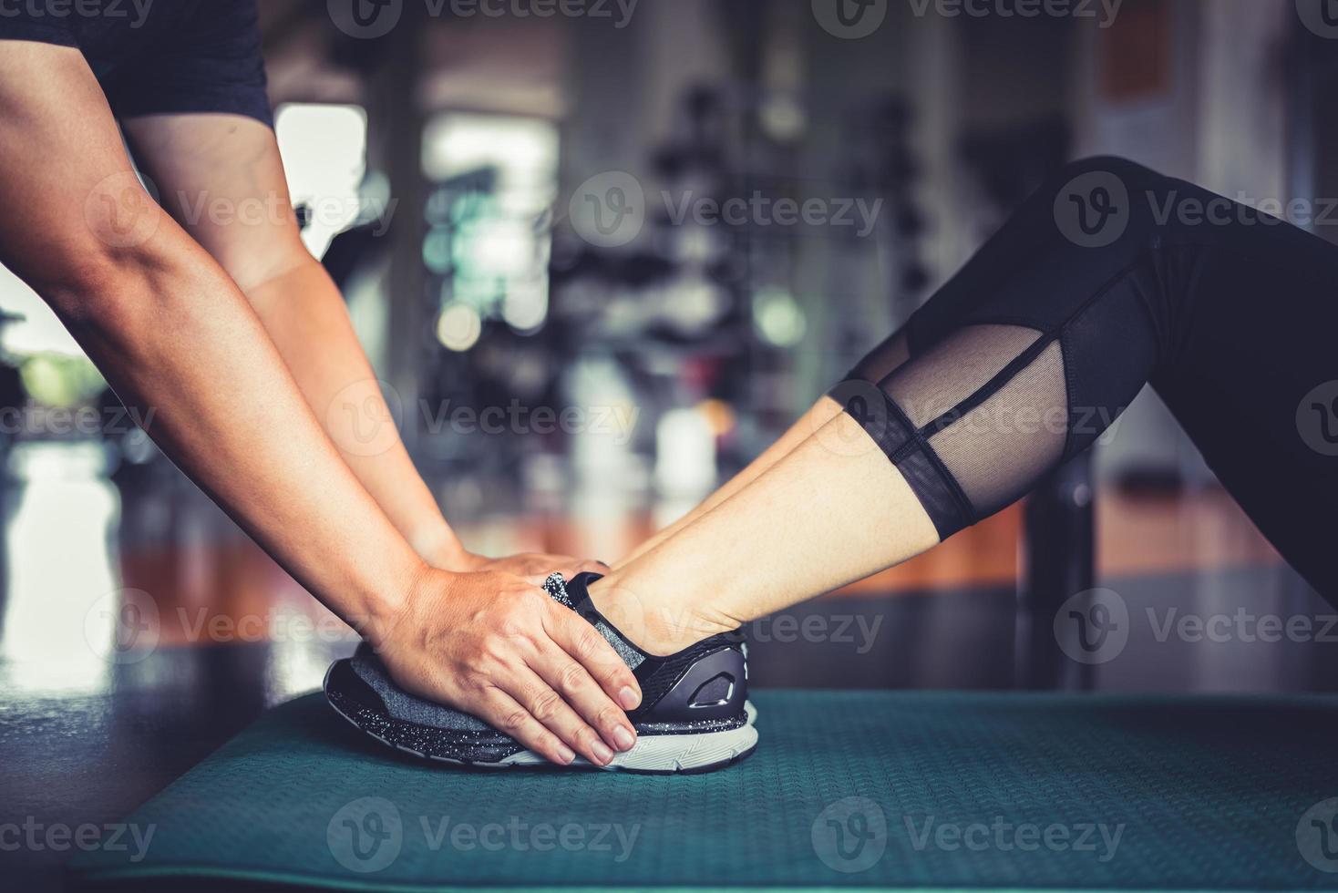 les mains d'un entraîneur de fitness aident une femme de fitness à s'entraîner à la torsion crunch photo