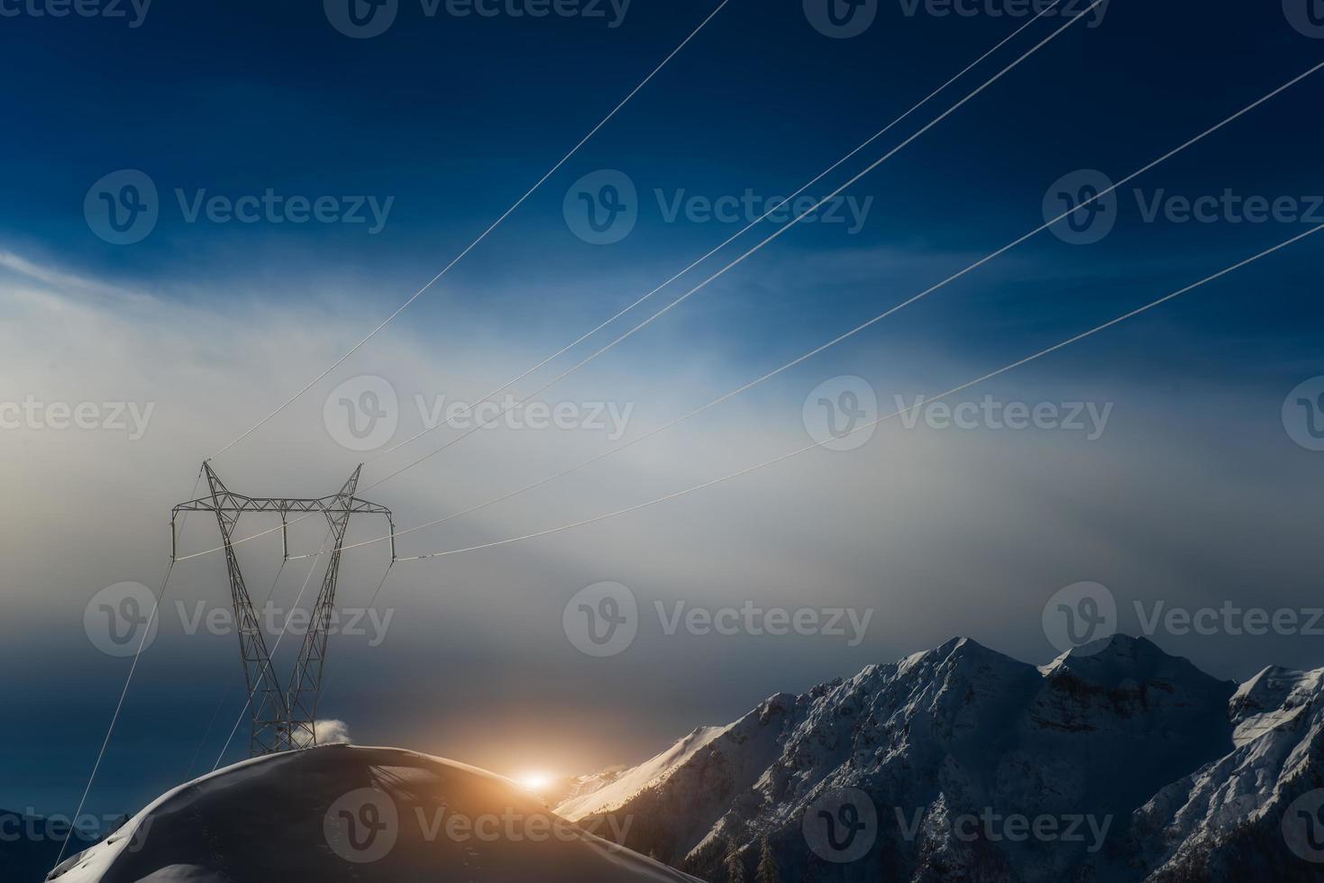 les pylônes recouverts de neige en haute montagne transportent l'énergie en aval photo
