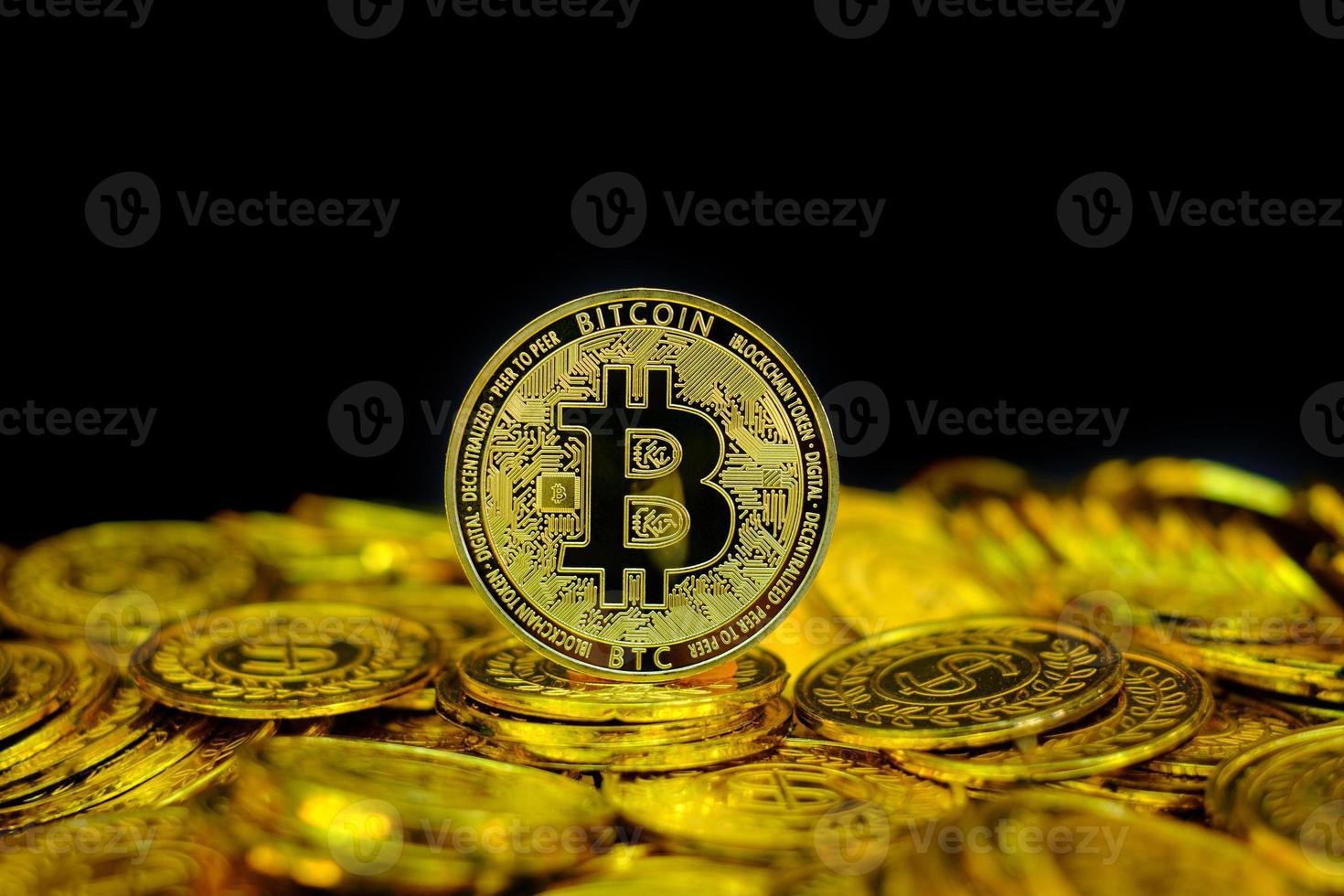 crypto-monnaie bitcoin d'or sur une pièce d'or de pile sur fond noir photo