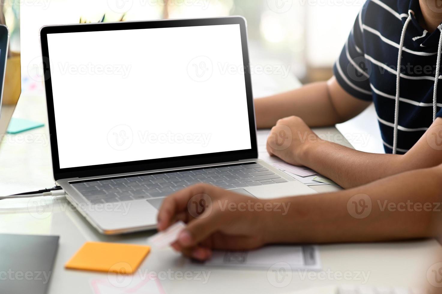photo recadrée d'un groupe de designers travaillant sur un ordinateur portable.