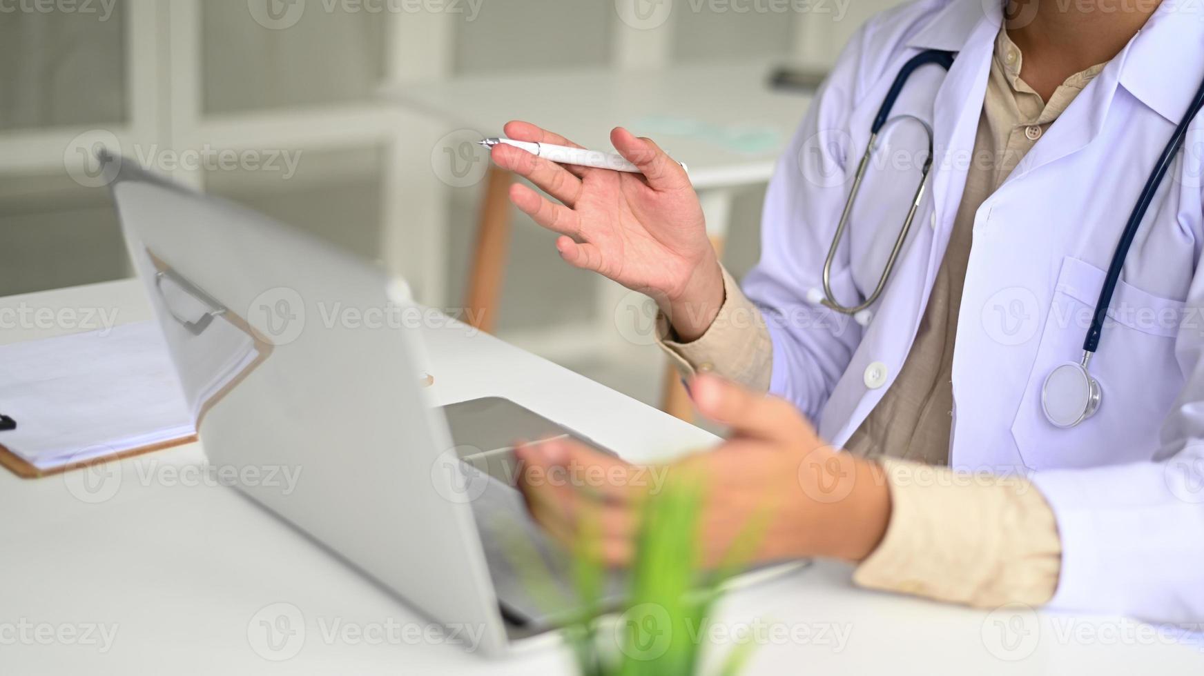 le personnel médical en blouse de laboratoire et stéthoscopes utilise des conférences sur ordinateur portable. photo