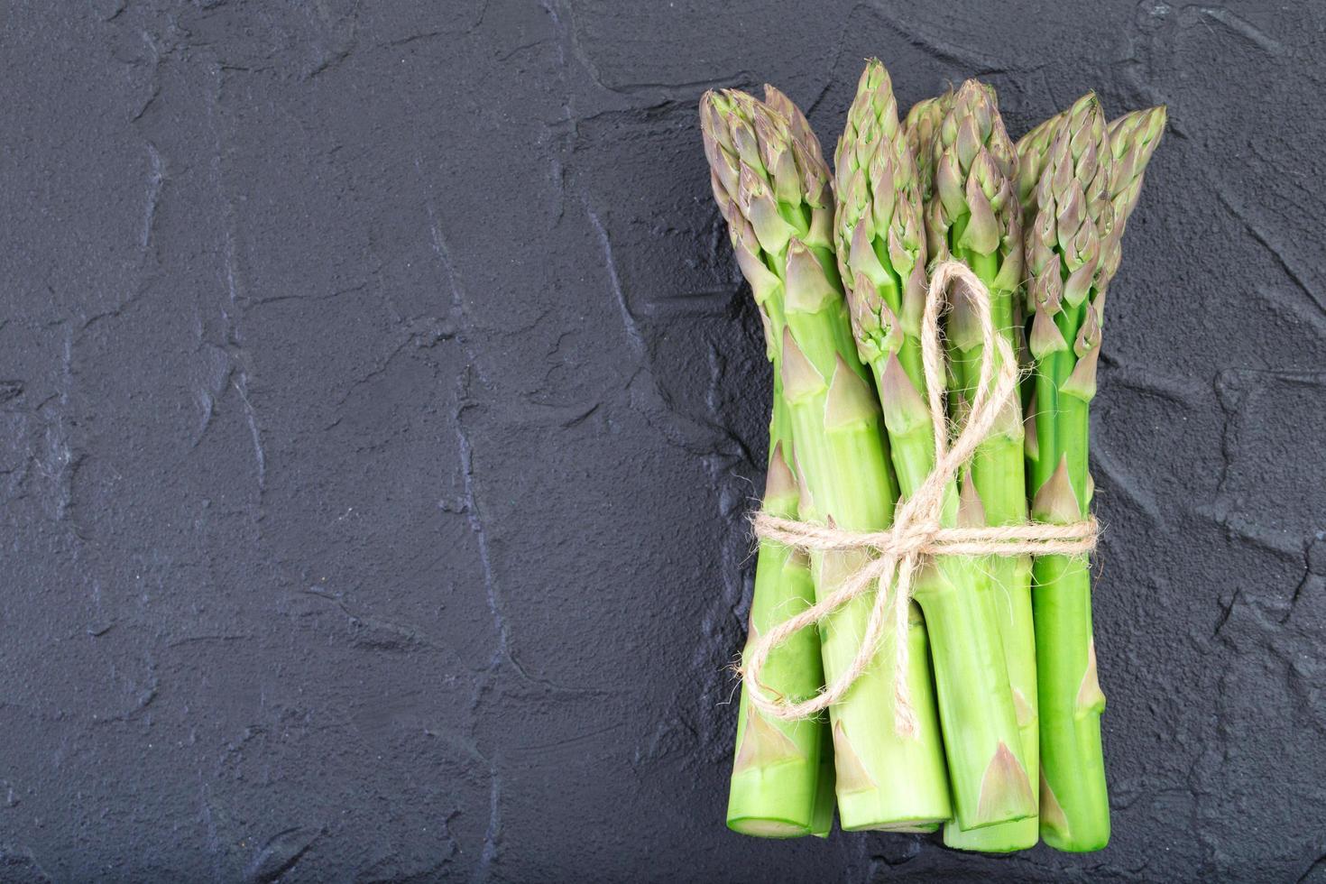 asperges vertes fraîches sur fond sombre photo
