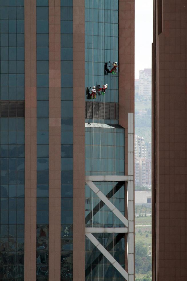 les vitres du gratte-ciel sont en train d'être nettoyées. photo