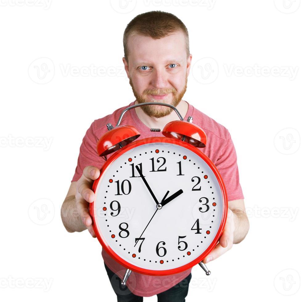 homme barbu tenant un réveil rouge photo