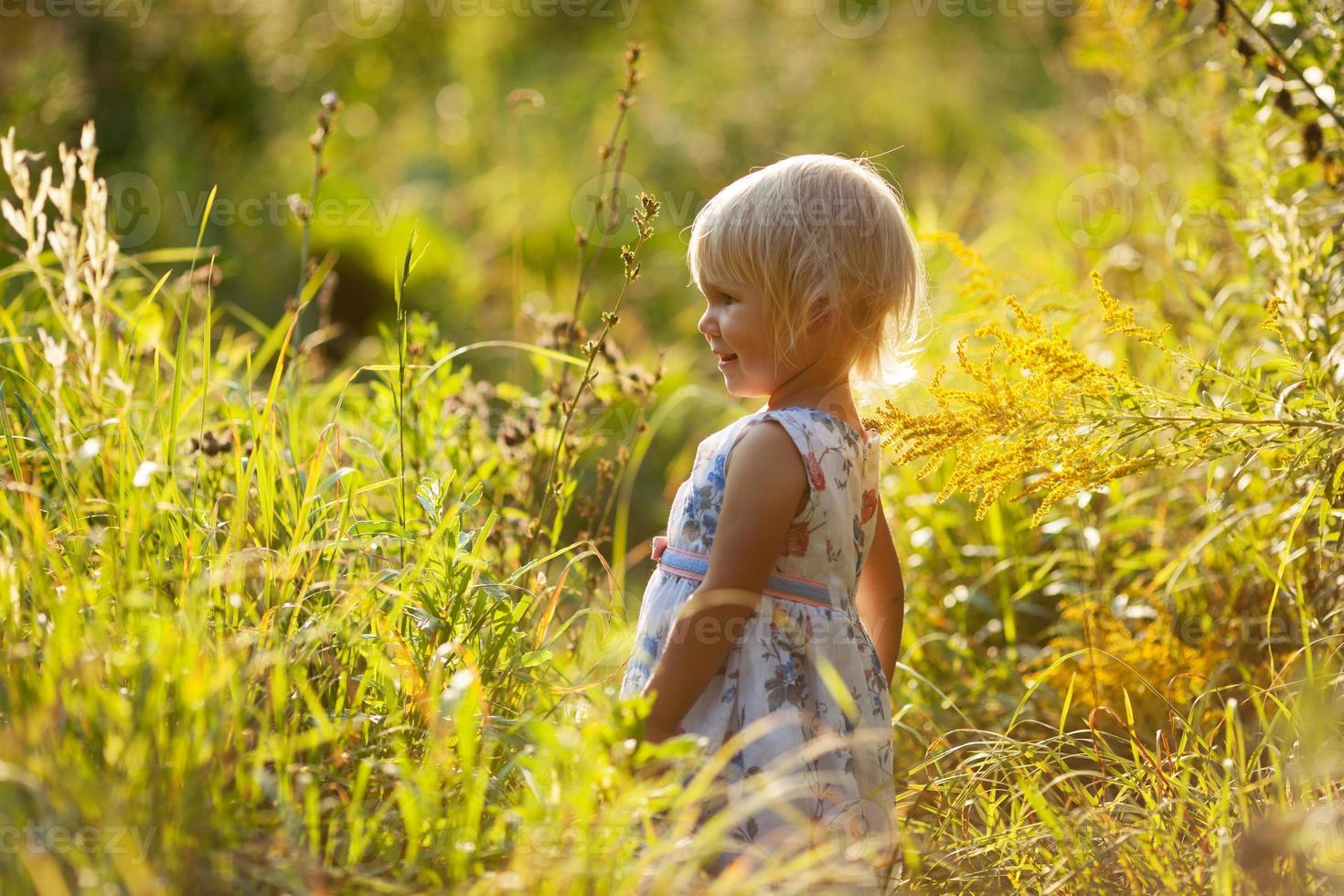 petite fille blonde en robe parmi les fleurs sauvages photo