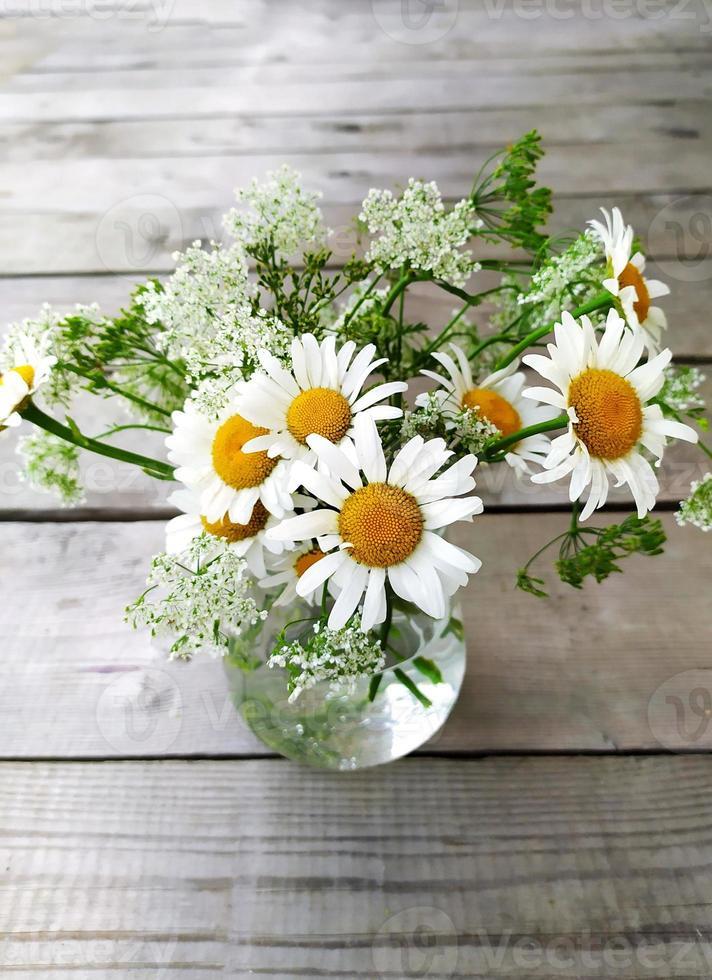 marguerites des champs sur un fond en bois. fleur de camomille dans un vase en verre. vue d'en-haut. belle nature morte d'été. photo