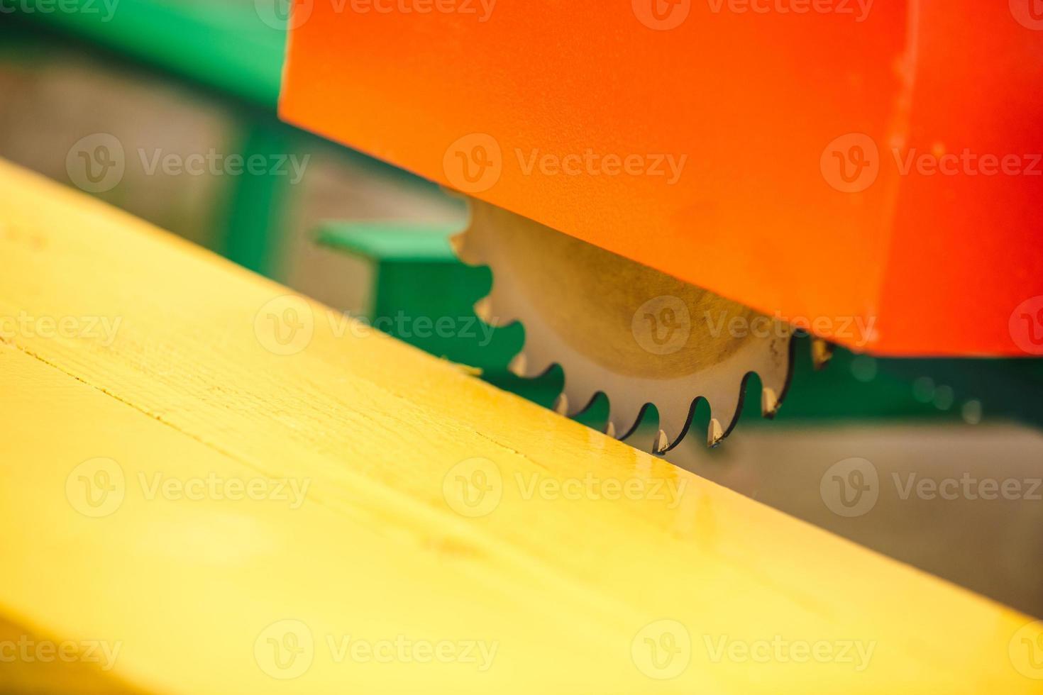 machine à couper le bois. gros plan scie circulaire électrique coupant du bois et une règle de fer. photo