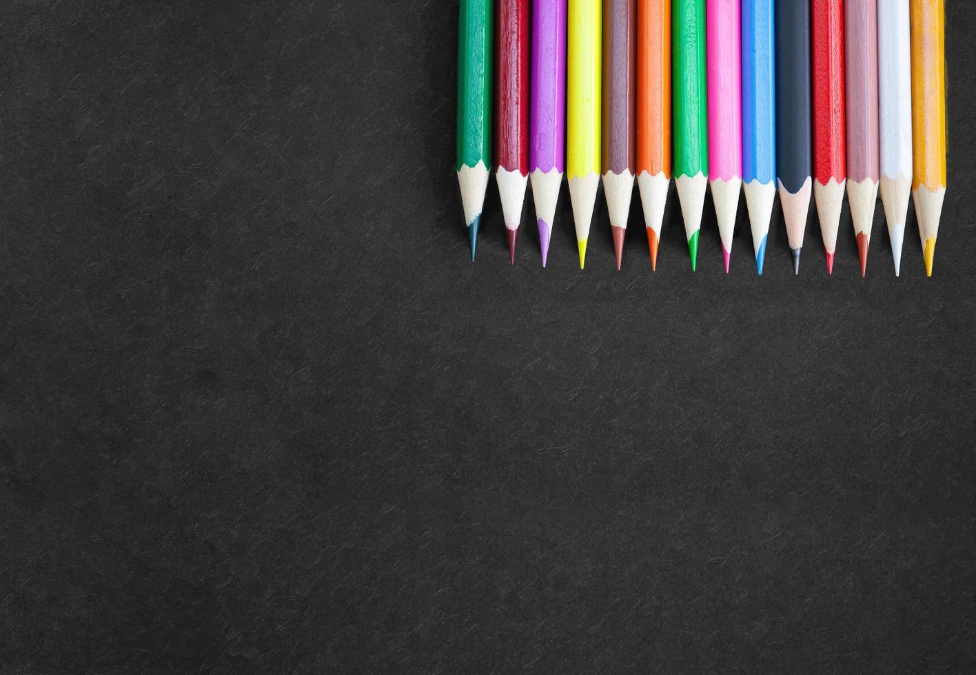 concept de bannière de dessin, crayons colorés dans le coin supérieur droit sur toile noire avec texture. photo