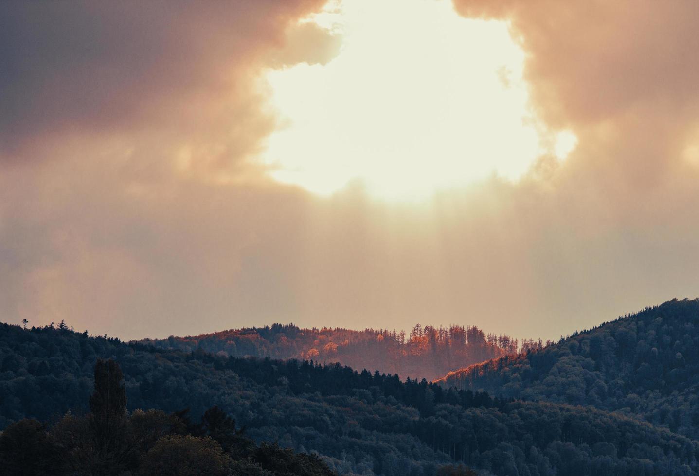 un trou dans le ciel - le soleil illumine le sommet de la montagne photo