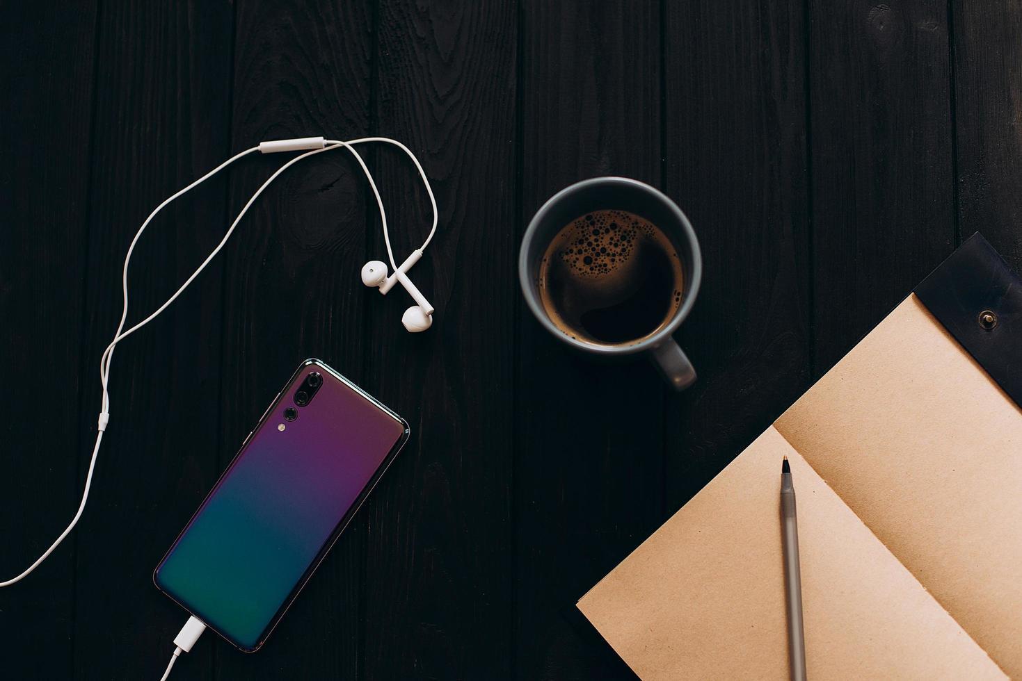 smartphone coloré lumineux sur un fond en bois noir. tasse de café du matin. photo