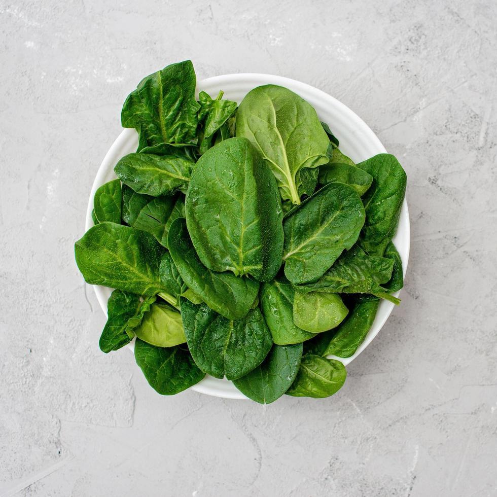 concept de nourriture propre. feuilles de légumes verts d'épinards biologiques frais dans une assiette sur fond clair. alimentation saine de désintoxication printemps-été. aliments crus végétaliens. photo