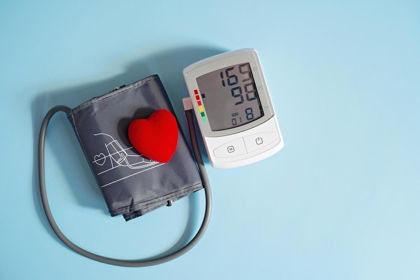 coeur de jouet rouge et tonomètre sur fond bleu. concept de soins de santé. cardiologie - prendre soin du cœur.. photo