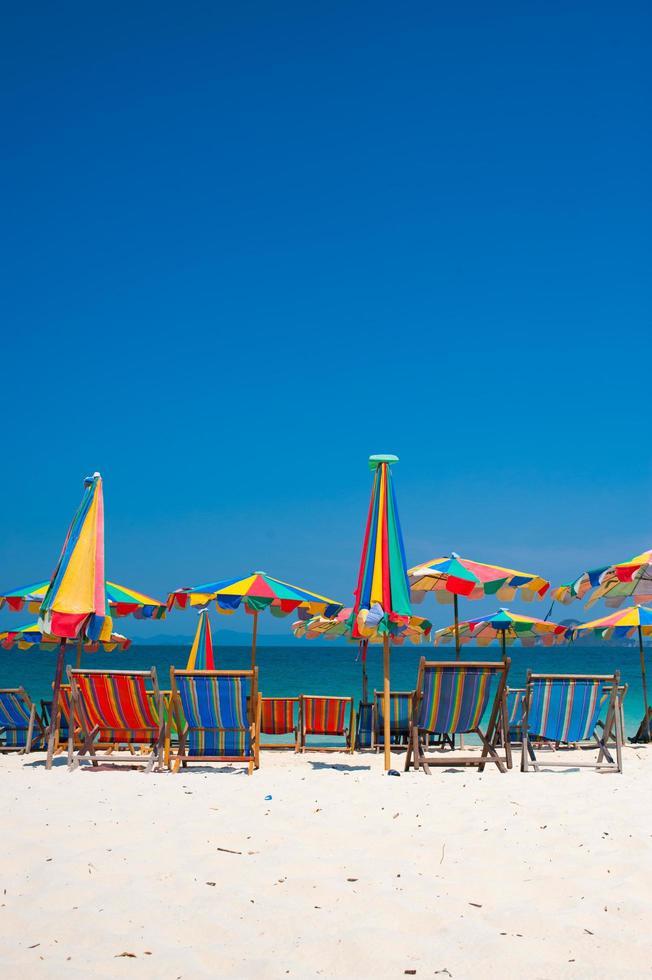 Chaise de plage sous l'égide de coloré sur la plage phuket, thaïlande photo
