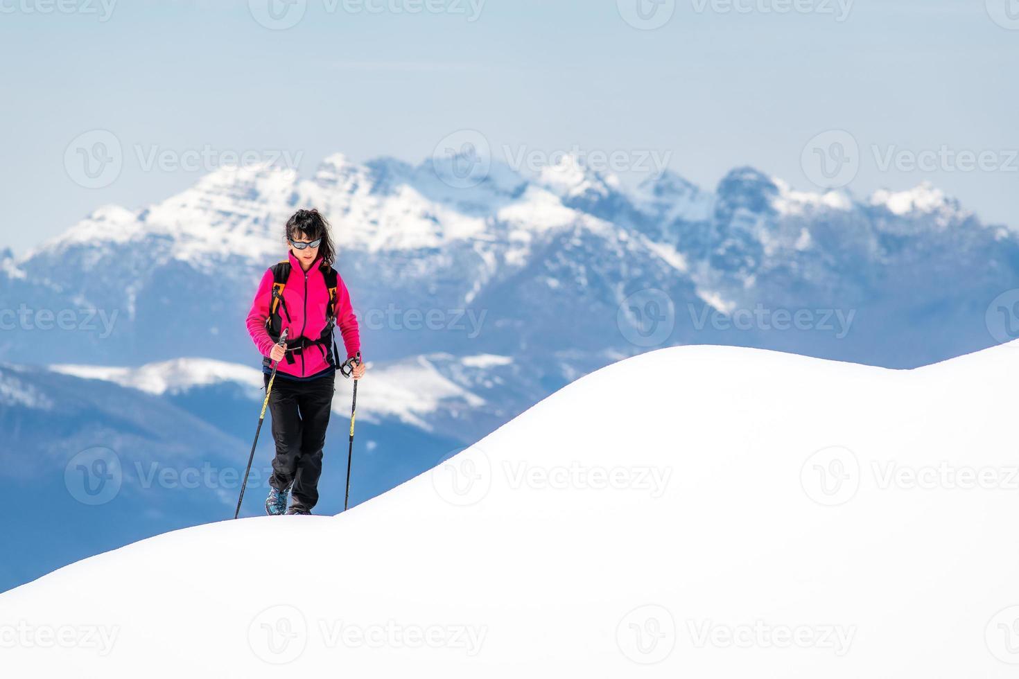 Jeune femme sur la crête de tant de neige s'élève vers le haut dans les montagnes photo