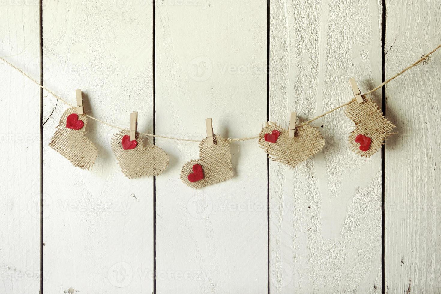 coeurs de jute heureux valentine accrochés à un mur en bois photo