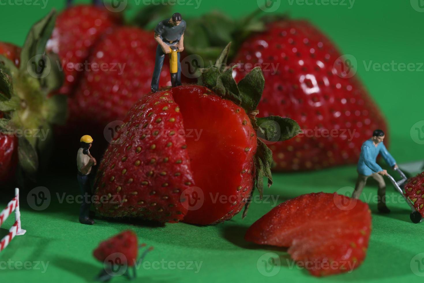 travailleurs de la construction dans l'imagerie alimentaire conceptuelle avec des fraises photo