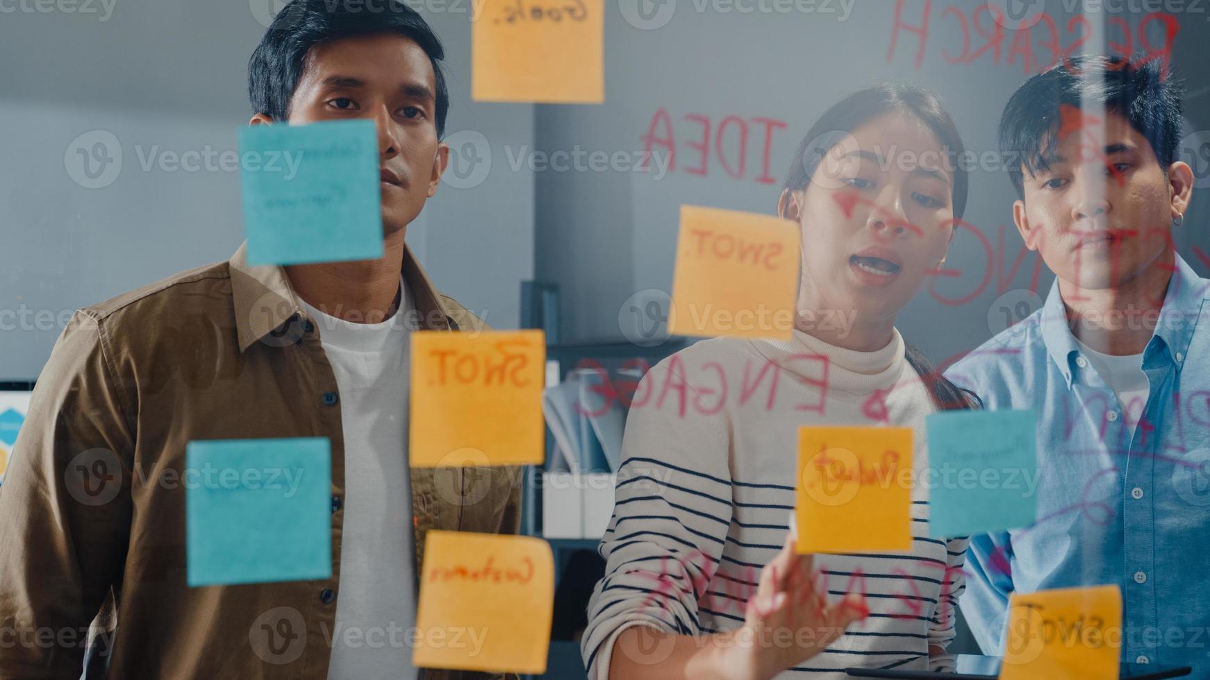 les hommes d'affaires d'asie se tiennent derrière un mur de verre transparent, écoutent le directeur pointant les travaux d'avancement et la réunion de remue-méninges et le travailleur publie une note collante sur le mur au bureau. inspiration d'affaires, partager des idées. photo