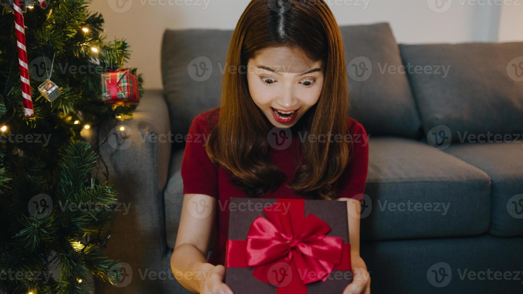 jeune femme asiatique s'amusant à ouvrir une boîte de cadeau de Noël près d'un arbre de noël décoré d'ornements dans le salon à la maison. joyeuse nuit de noël et bonne année festival de vacances. photo
