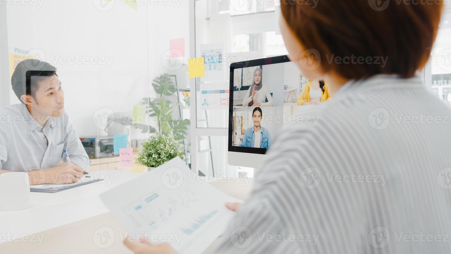 les hommes d'affaires asiatiques utilisant le bureau parlent à des collègues discutant d'un remue-méninges d'entreprise sur le plan d'une réunion par appel vidéo dans un nouveau bureau normal. mode de vie distanciation sociale et travail après le virus corona. photo