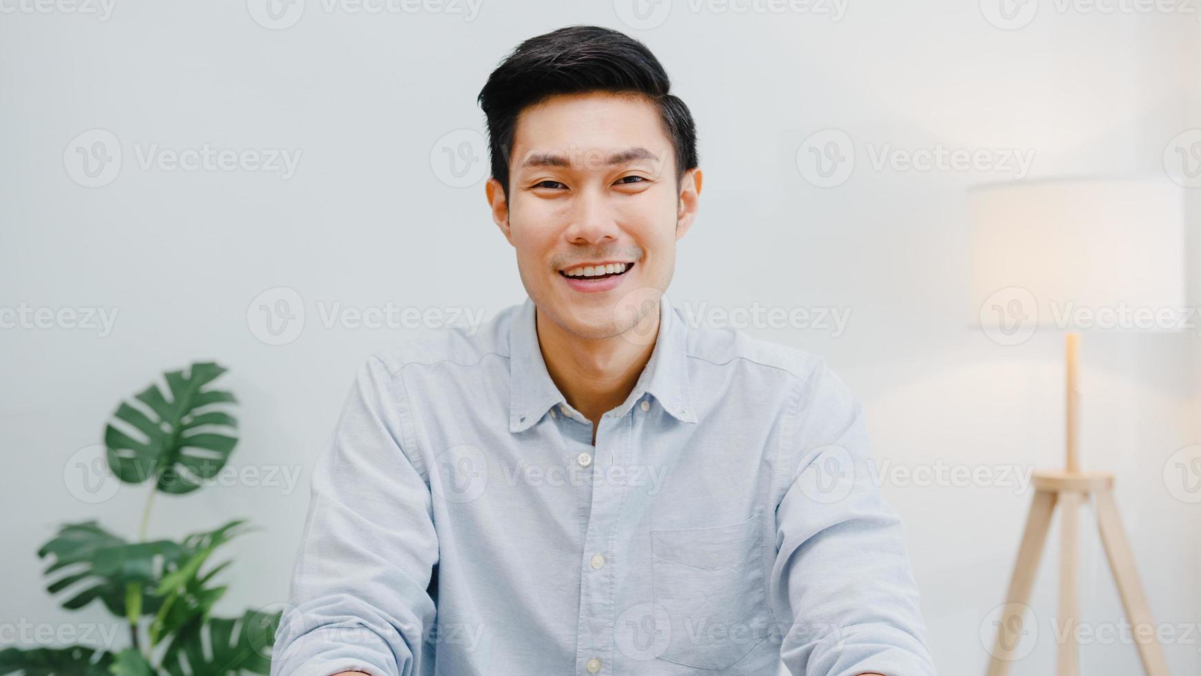portrait d'un bel homme d'affaires exécutif réussi, vêtements décontractés intelligents, regardant la caméra et souriant, heureux dans un lieu de travail de bureau moderne. un jeune asiatique parle à un collègue lors d'une réunion par appel vidéo à la maison. photo