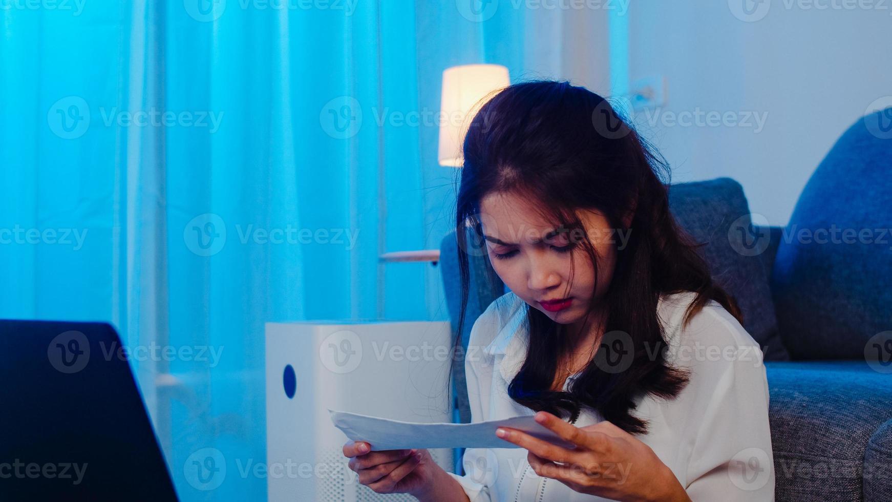 les femmes asiatiques fatiguées se sentent stressées à cause de problèmes financiers à la maison. travail à domicile surchargé la nuit, travail à distance, auto-isolement, distanciation sociale, quarantaine pour la prévention des coronavirus. photo