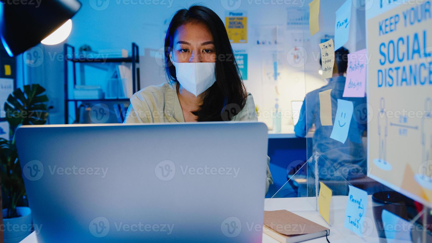 femme d'affaires asiatique heureuse portant un masque médical pour la distanciation sociale dans une nouvelle situation normale pour la prévention des virus tout en utilisant un ordinateur portable au travail la nuit au bureau. vie et travail après le coronavirus. photo