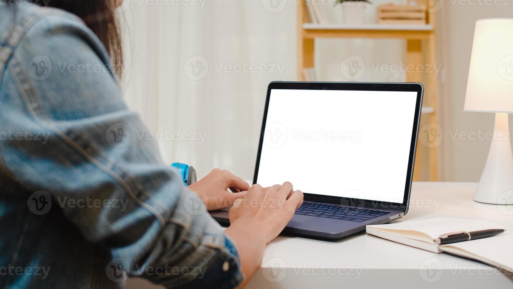 jeune femme asiatique créative assise à son bureau à l'aide d'un ordinateur portable avec une maquette d'écran blanc dans le salon confortable d'une maison moderne. photo