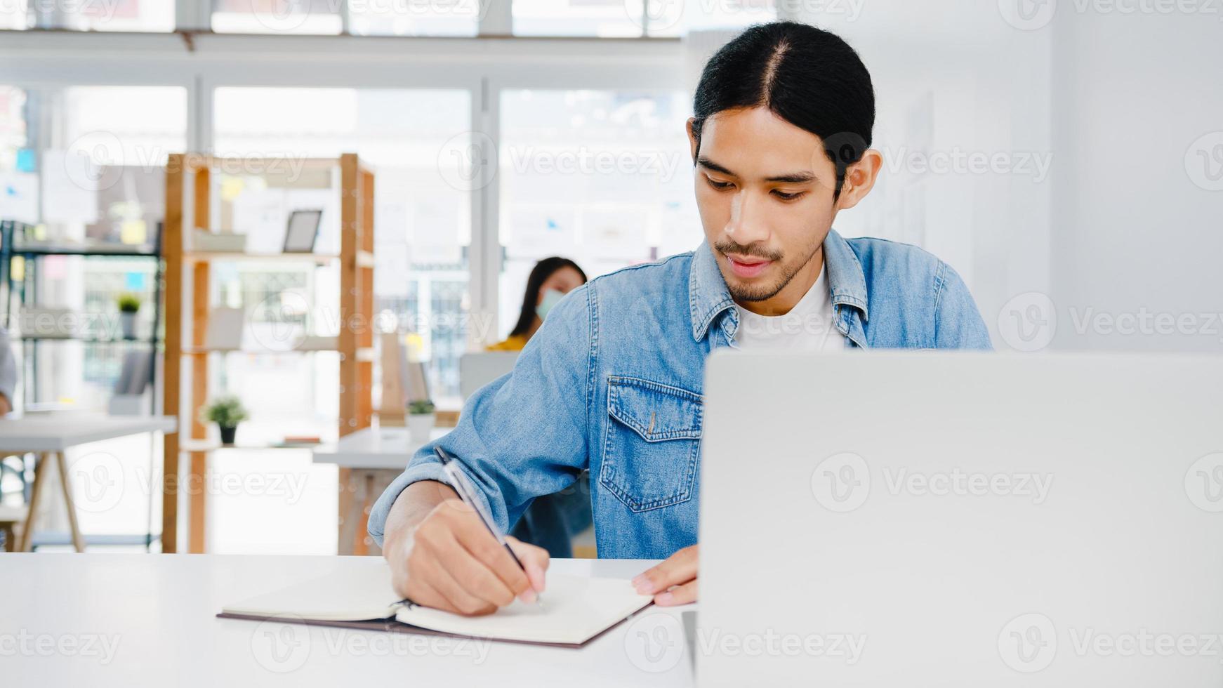 homme d'affaires asiatique distanciation sociale dans une nouvelle situation normale pour la prévention des virus à l'aide d'une présentation d'ordinateur portable à un collègue sur le plan d'un appel vidéo pendant qu'il travaille au bureau à domicile. mode de vie après le virus corona. photo