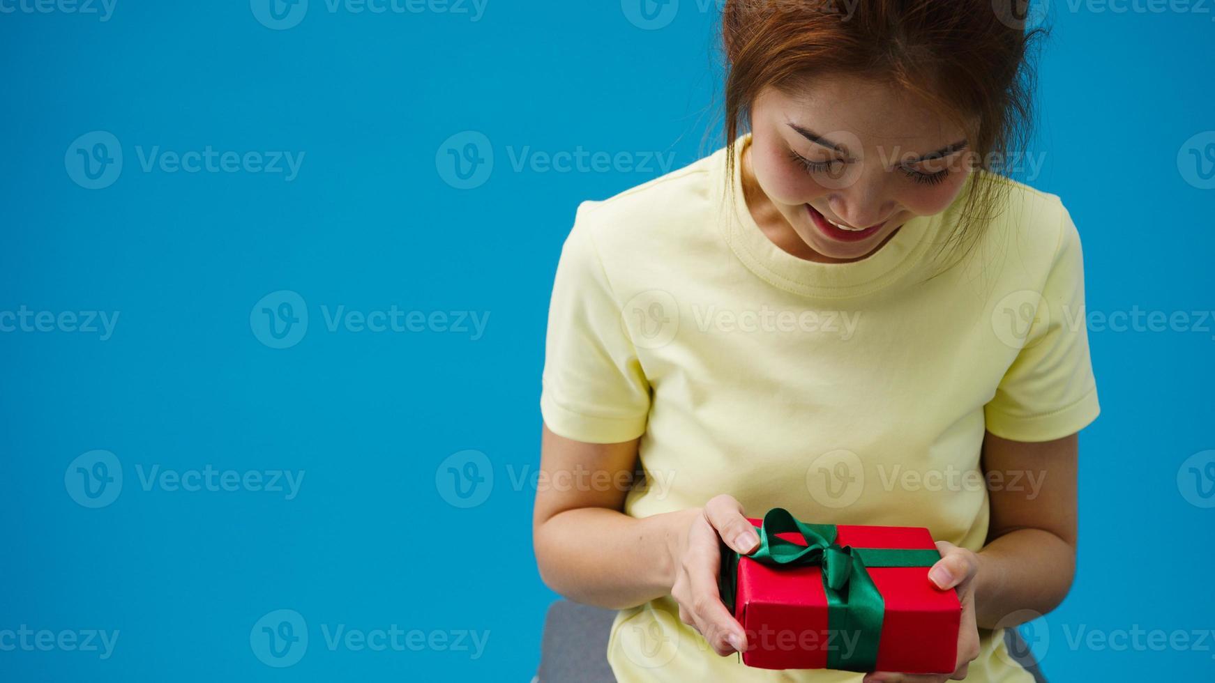 jeune fille asiatique souriante et recevant une boîte présente isolée sur fond bleu. copiez l'espace pour placer un texte, un message pour la publicité. zone publicitaire, maquette de contenu promotionnel. photo