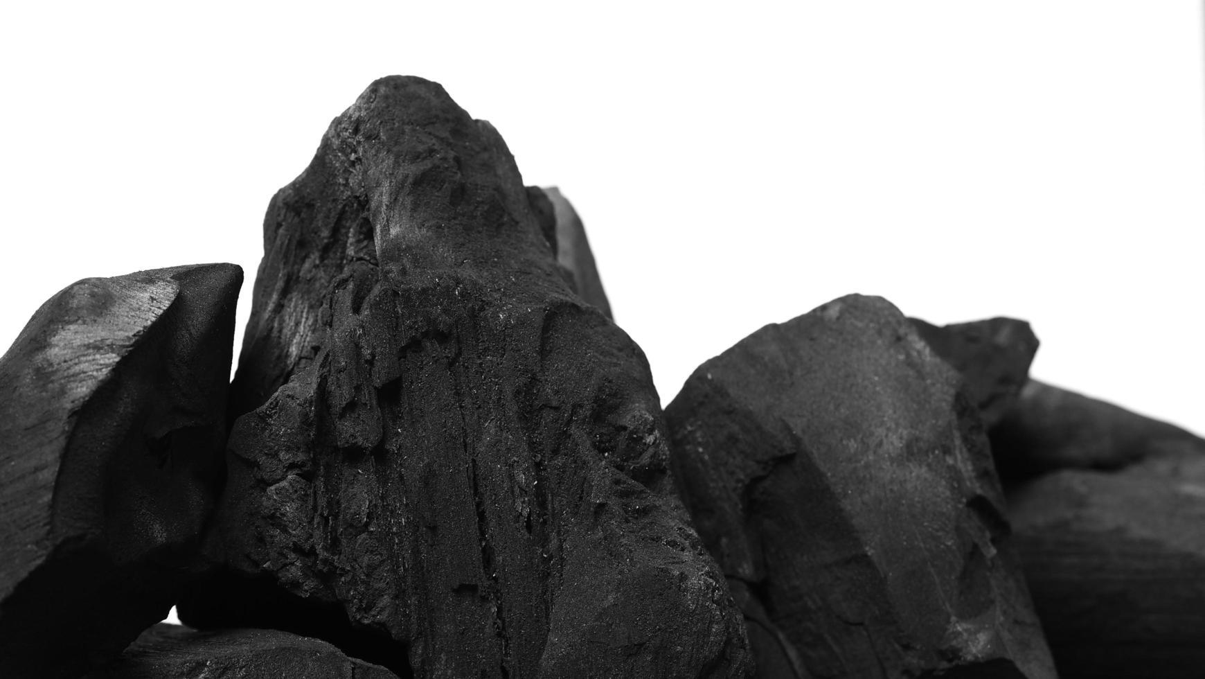 charbon de bois. charbon de bois noir sur sol texturé noir. utilisé pour la cuisine photo
