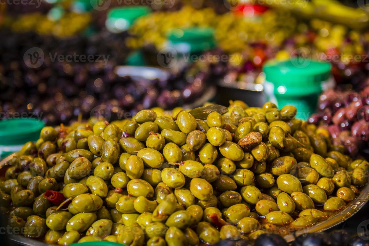 olives à un étal de marché. une variété de types d'olives photo