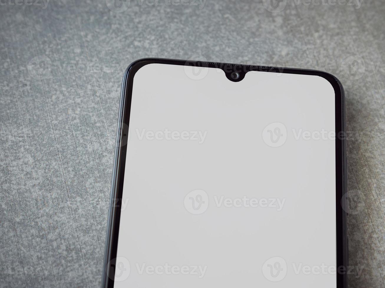 maquette de smartphone mobile noir se trouve à la surface avec un écran blanc isolé sur un fond de pierre céramique granit porcelaine photo