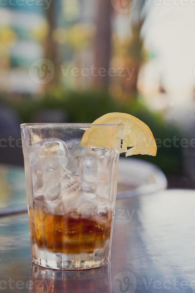 verre avec du cola, de la glace et du citron sur une table à l'extérieur photo