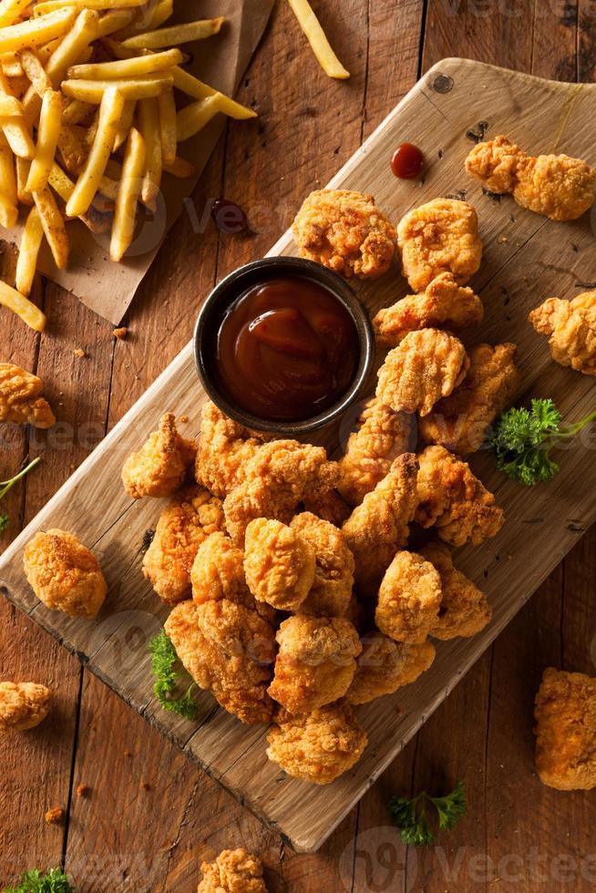 poulet pop-corn croustillant et frites sur une planche de bois photo