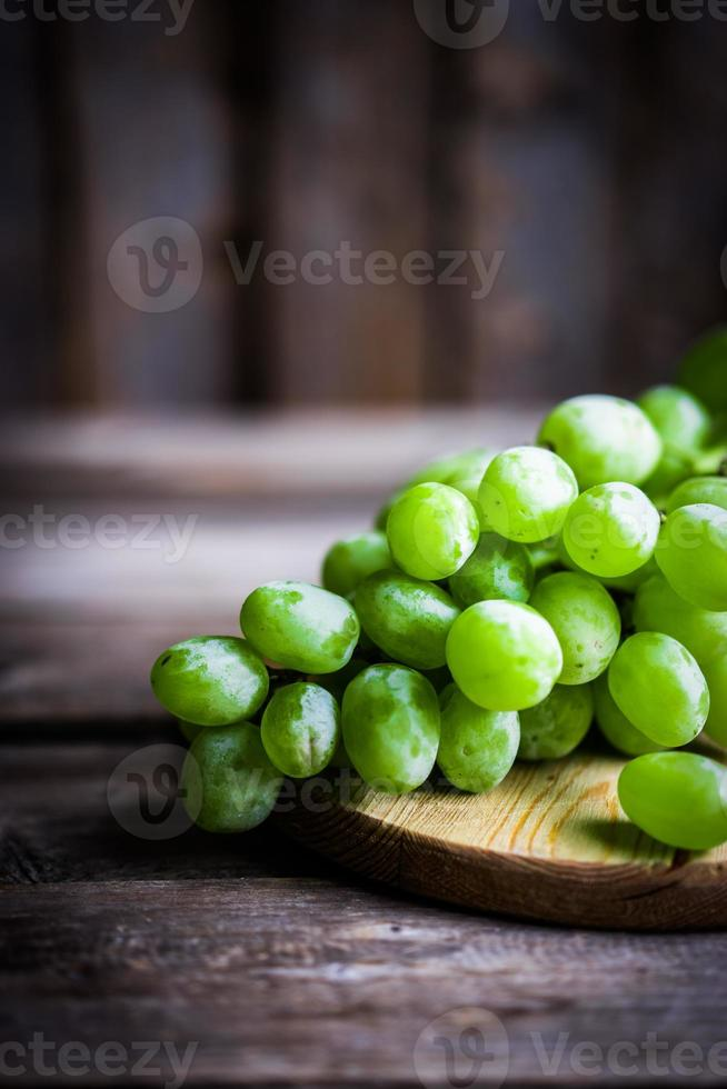 vigne de raisins verts sur fond de bois rustique photo