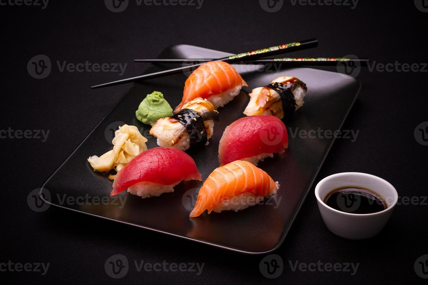 Sushi d'anguille, de saumon et de thon avec des baguettes photo