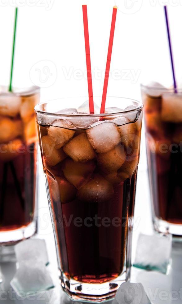 trois verres de cola avec de la glace et des pailles photo