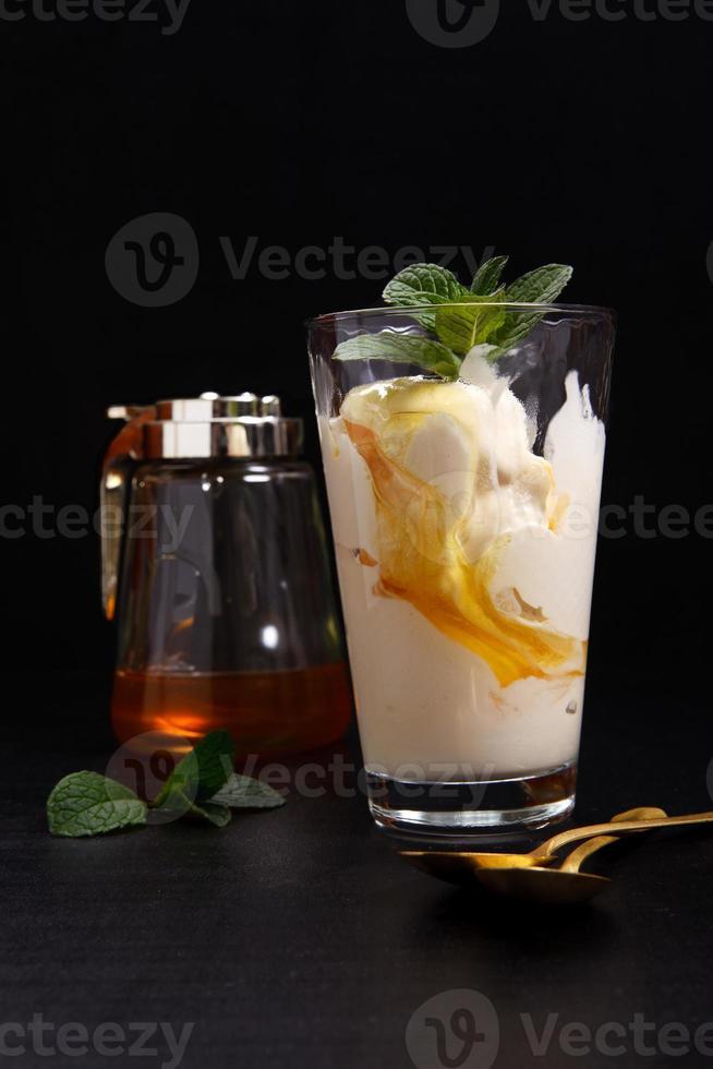 crème glacée dans un verre avec du miel sur un fond sombre photo
