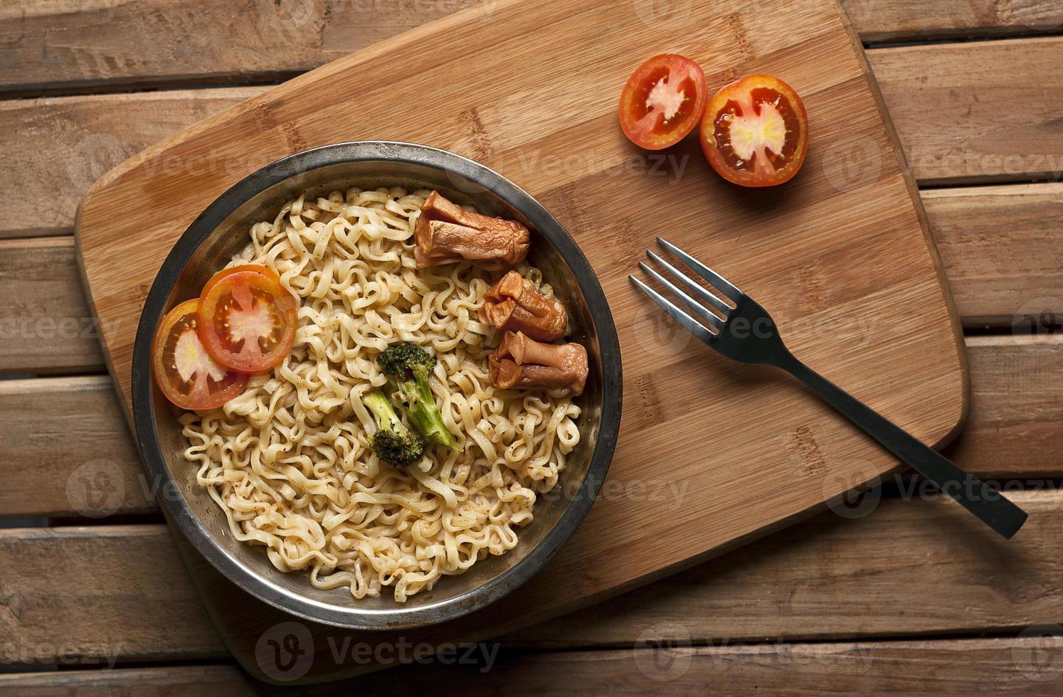 nouilles à la tomate et à la saucisse dans un bol en acier inoxydable photo