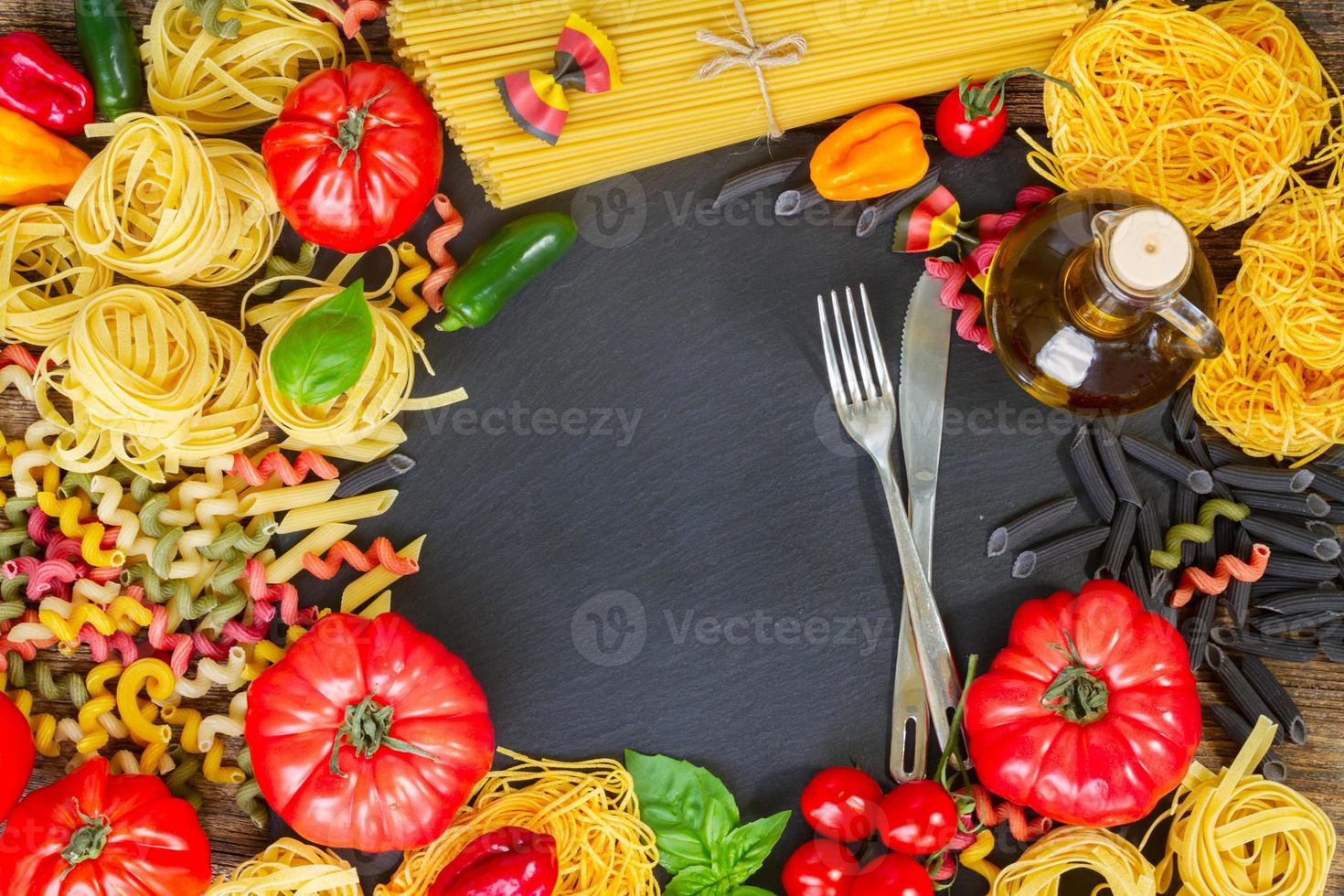 pâtes crues avec ingrédients sur tableau noir photo