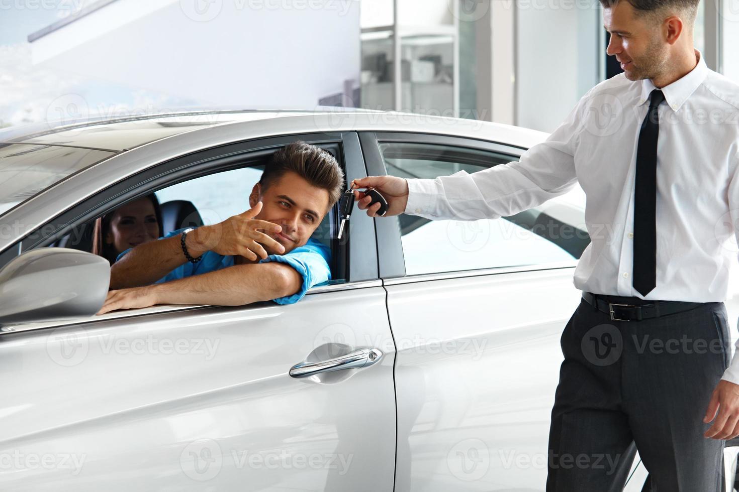 consultant en vente montrant une nouvelle voiture à un acheteur potentiel photo