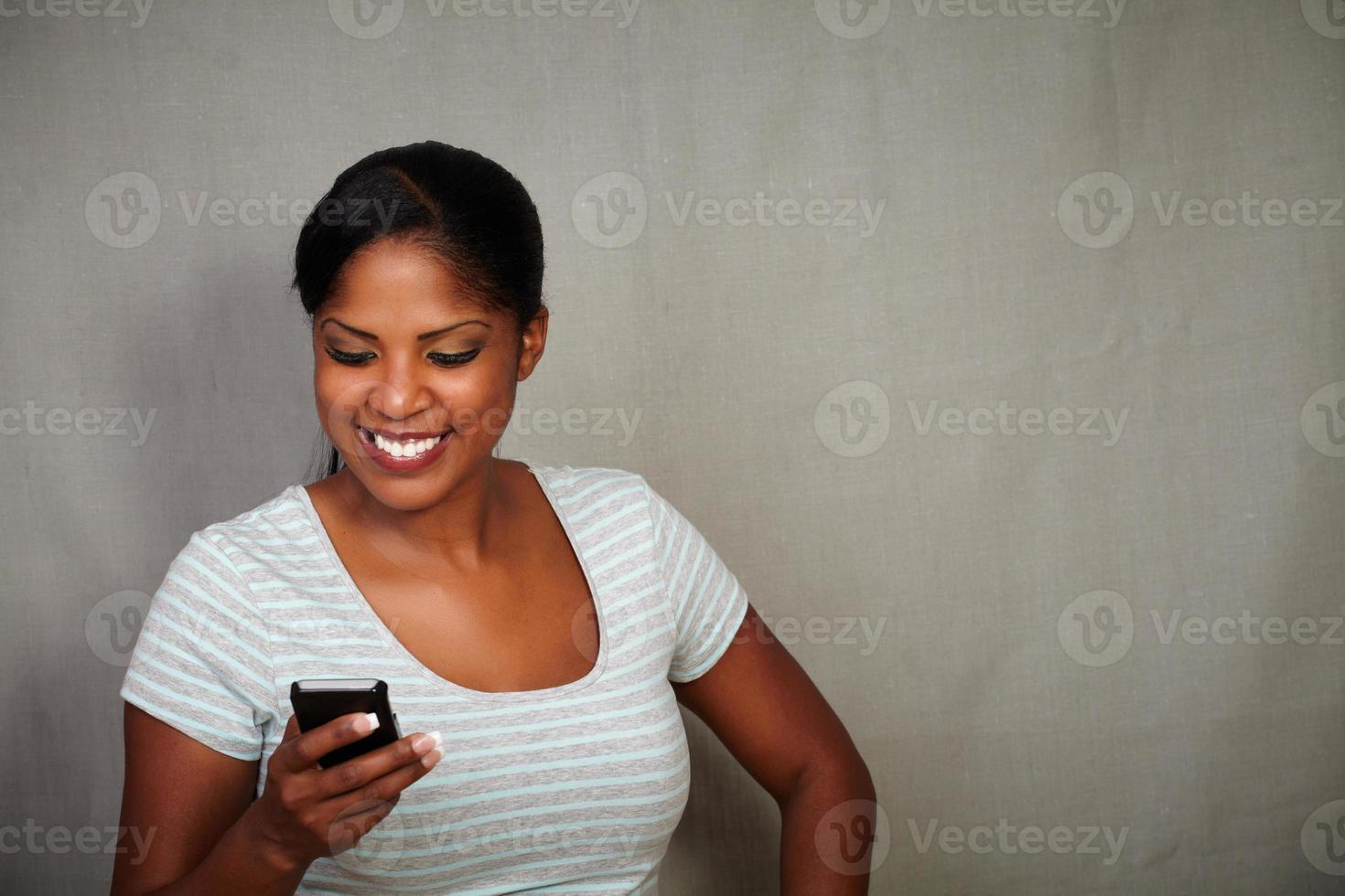 fille souriante, envoyer des SMS sur son téléphone portable photo