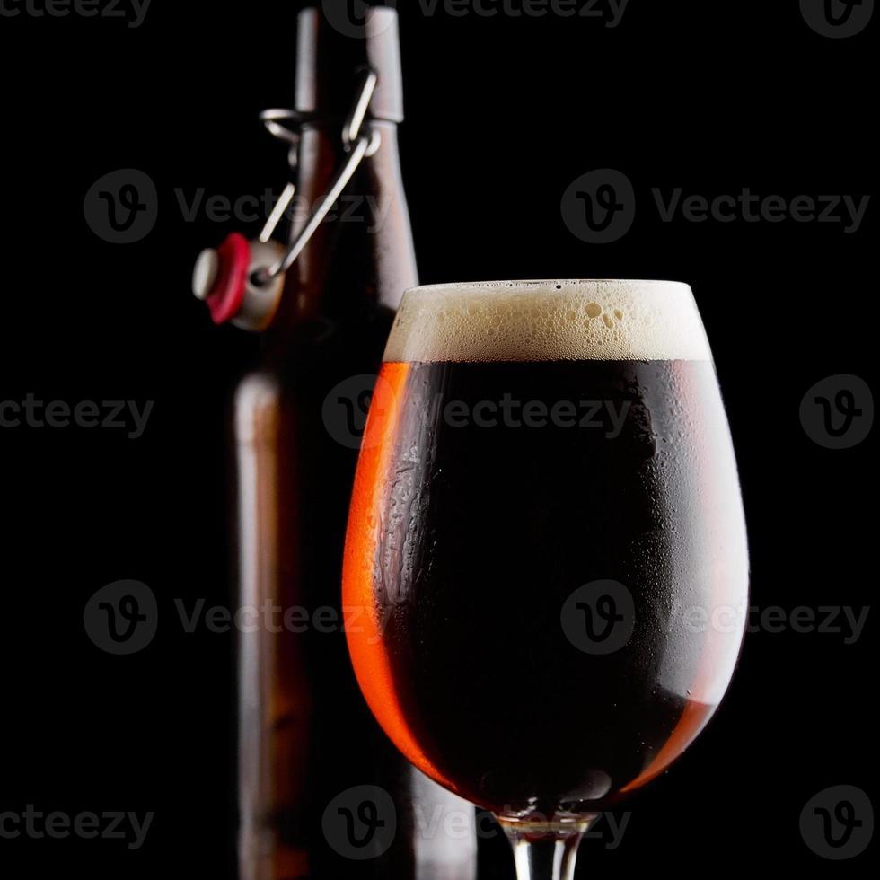 bière en verre sur fond noir photo