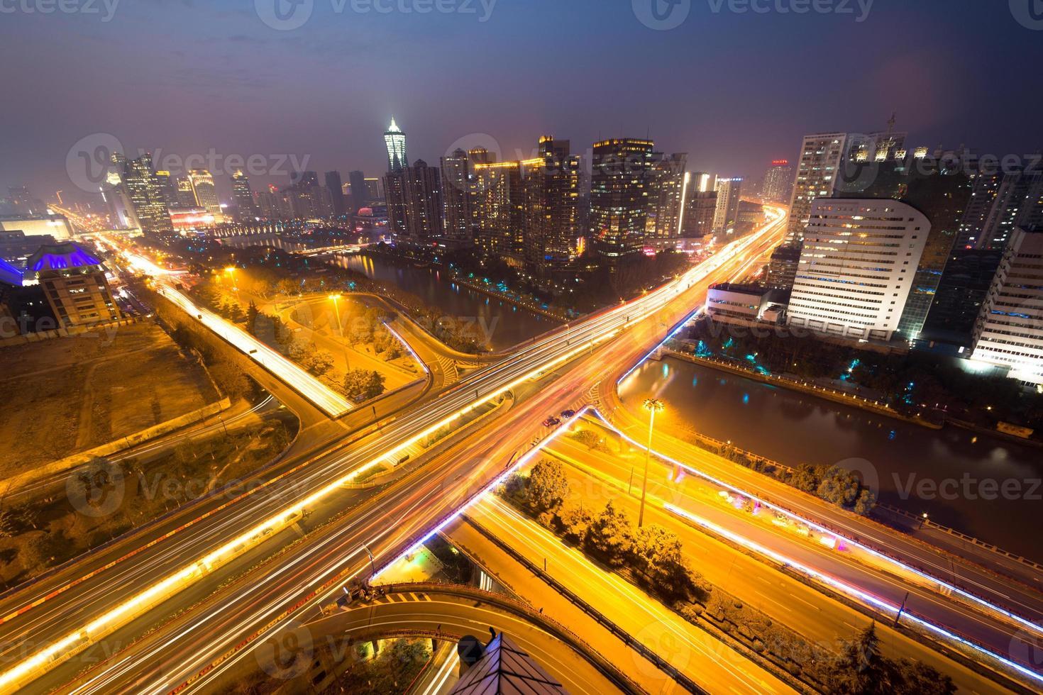 sentiers de feux de circulation sur le viaduc et le paysage urbain la nuit photo